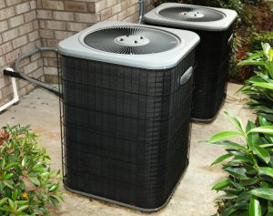 two outdoor units of an air conditioner sitting on a concrete slab