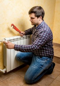 man with wrench preparing to work on radiator in home