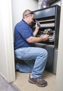 technician working on the inside of a furnace