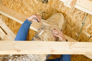 A worker is sealing two sections of house attic vent duct insulation with aluminum foil tape. The foreground is a section of truss and the background is OSB sheathing for the roof.