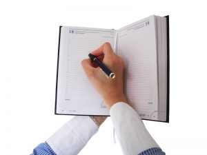 female hands writing in monthly planner on white background