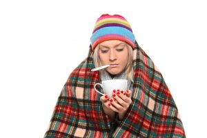 woman wrapped in blanket holding cup of tea, and thermometer in mouth