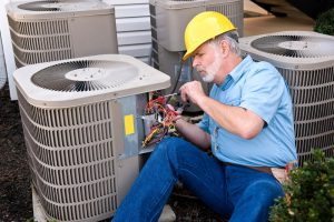 HVAC technician in hard hat working on AC unit