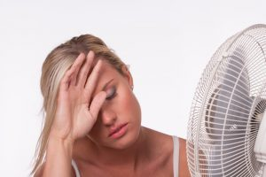 woman looking warm in front of fan