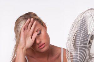 woman looking warm in front of fan