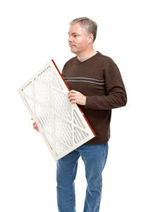 man holding air filter on a white background