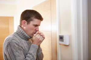 man looking cold in front of thermostat
