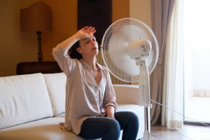 woman-sitting-in-front-of-fan-cooling-off